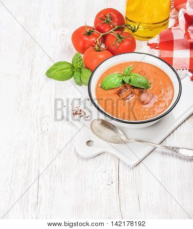 Cold gazpacho soup in bowl with ice, hot pepper and basil served with fresh tomotoes on ceramic board over white wooden background, top view, selective focus, copy space, vertical composition