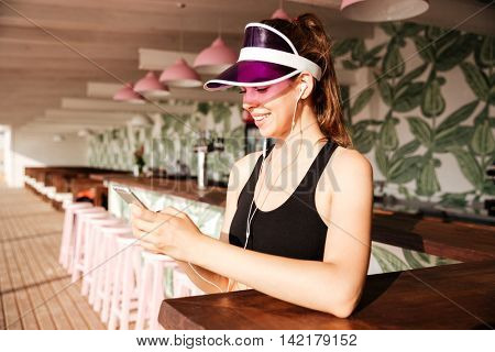 Young attractive sports woman listens music with earphones and smartphone in her hands in cafe