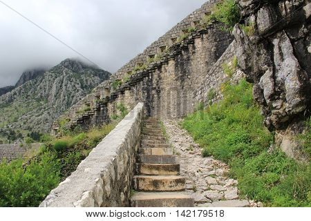 A long stone staircase with high steps rising up to the clouds