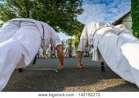 Miskolc Hungary - August 2. 2016: Athletes are pressed on the asphalt ground during the international summer training camp for Kyokushin Karate.