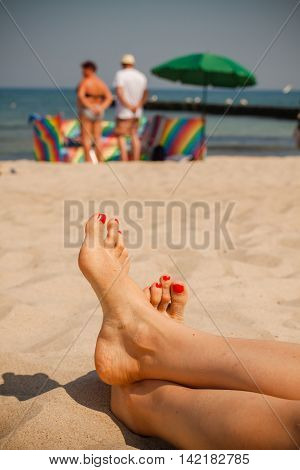 Women feet on the beach. In the background sunbathers with umbrellas and windbreaks.