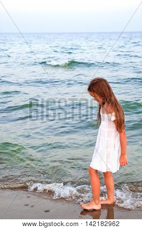 Adorable little girl is walking on the sea coast on vacation