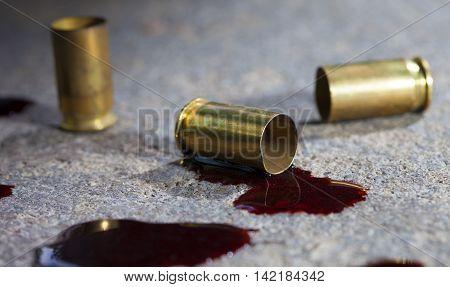 Three piece of handgun brass with blood on concrete