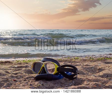 Diving mask with snorkel on a sandy beach against the sea and sky in the morning