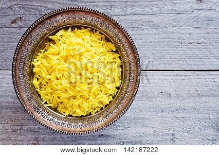 Top view of an antique metal bowl with cooked turmeric jasmine rice on an old wooden table