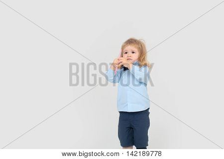 Little boy cute child with sad serious face long blond hair in blue shirt and shorts holding colored pink pencil on white background isolated