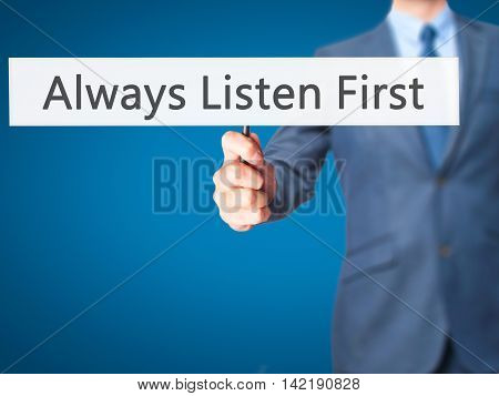 Always Listen First - Businessman Hand Holding Sign