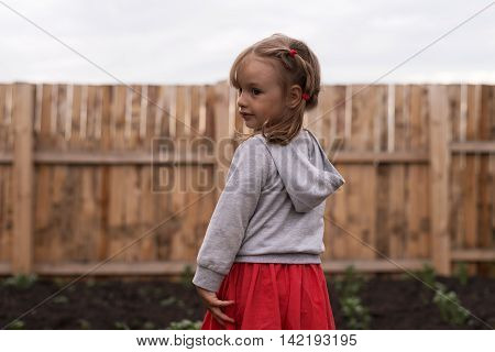 Little three-year-old girl in the garden standing against a wooden gence background.
