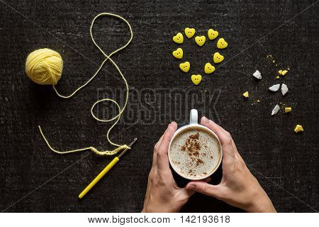 Female hands with a cup of coffee, yellow crocketing and a heart made of buttons on a grunge black background.