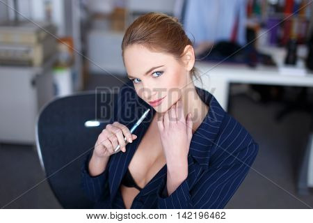 Sexy tempting secretary holding pen in office and smile