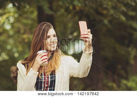 Cheerful young millennial blonde Caucasian woman holding cup of takeaway coffee, taking a selfie in park in autumn using smart phone. Matte color filter, medium retouch, natural light.