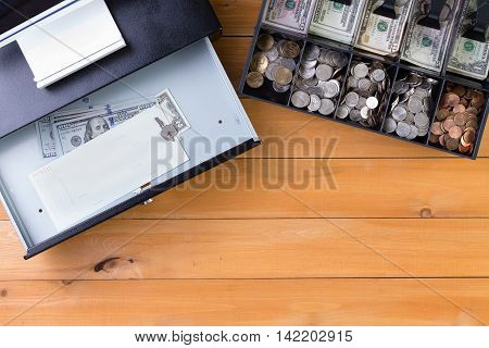 Top down view on separate cash drawer stocked with coins and American dollars beside open register with key and large denomination bills on wooden table. Includes copy space. poster
