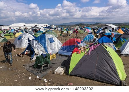 IDOMENI, GREECE - MARCH 17, 2016: Refugees from Syria sit by their tents on March 17 2015 in the refugee camp of Idomeni Greece. For several weeks more than 10.000 refugees and immigrants wait here for the borders to open.