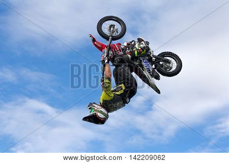 WEEDON, UK - AUGUST 27: A rider performing freestyle FMX stunts completes a full 360 degree loop on a minibike for the watching public at the Bucks County show on August 27, 2015 in Weedon