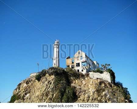 San Francisco, USA - October 22, 2008: Rocky outcrop on Alcatraz island, with the lighthouse and the Alcatraz prison social hall on the top  (San Francisco, California, USA)