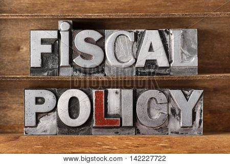 fiscal policy phrase made from metallic letterpress type on wooden tray poster