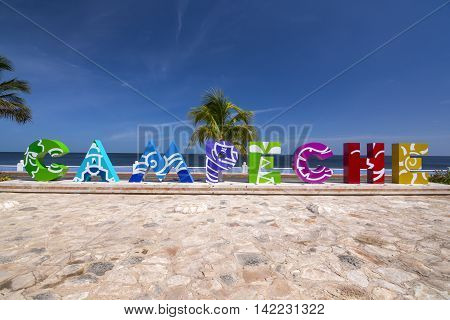 CAMPECHE, MEXICO - JULY 7, 2016: Big colorful letters spelling Campeche offer tourists a selfie-photo opportunity with a beautiful blue sea and coconut palms in the background