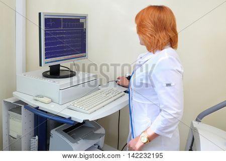nurse examines cardiogram of patient monitor ECG in multidisciplinary clinic