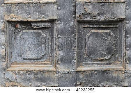 metal vintage door with peeling paint and with relief in form of rectangle, closeup