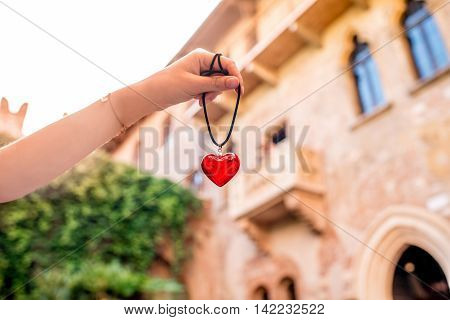 Holding a decoration in form of heart with Romeo and Juliet balcony on the background in Verona city