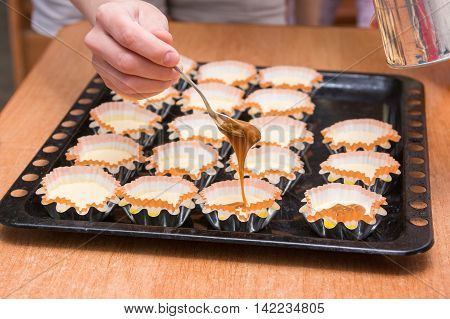 Boiled Condensed Milk Added To Raw Cupcakes Workpiece Lying On A Baking Sheet