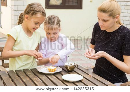 Mother And Two Daughters Are Preparing For The Holiday Easter Cupcakes