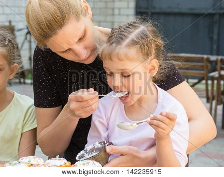 Mother Feeding Daughter With Spoon Confectionery Glaze For Cooking Cakes