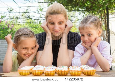Mother And Two Daughters With A Good Appetite And Big Eyes Looking At Easter Cupcakes