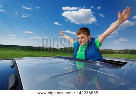 Portrait of happy smiling five years old boy enjoying freedom on the sunroof of a car