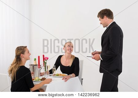 Waiter Taking An Order From Happy Female Friends In restaurant