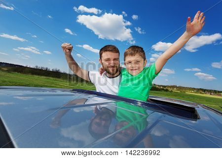 Portrait of happy family, father with his five years old son, enjoying freedom on the sunroof of their car, against beautiful landscape