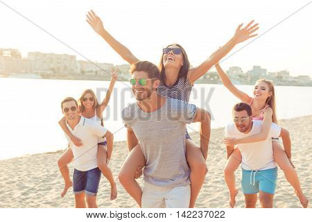 Outdoors Photo Of Happy Boyfriends Piggybacking Their Girlfriends At Sunset On Beach