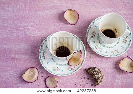 Two empty coffee cups and rose petals copy space background