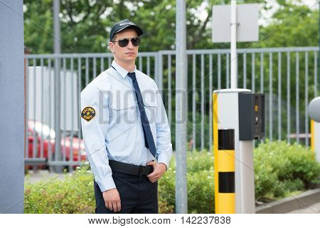Young Male Security Guard Standing Beside Car Parking Machine