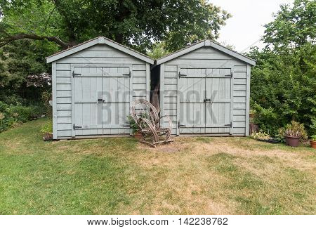 Wooden garden sheds with trees in background