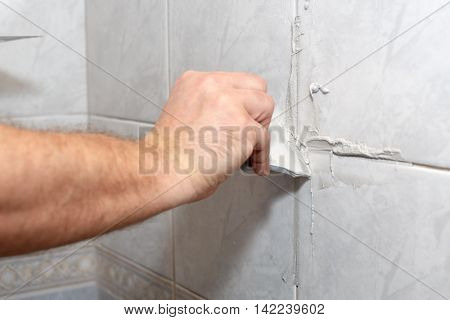 The male hand with the rubber spatula applies grout on a seam between tiles in a bathroom. Home repairs.