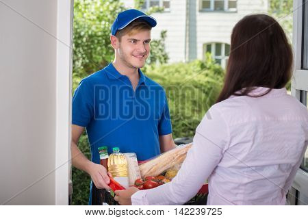 Woman Receives Groceries From The Delivery Man At Home