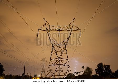 Lightning striking behind palm trees in the distance. A power tower and lines stand tall in the foreground. It is a stormy summer night in the Arizona desert during monsoon season.