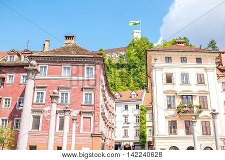 Old buildings with castle tower and slovenian flag in Ljubljana city