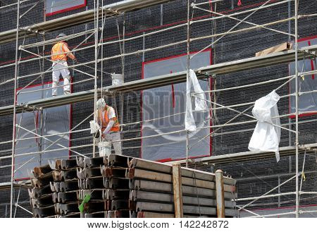 Two construction workers in hardhats and safety vests working on scaffolding with dark background. Iron beams in  foreground.