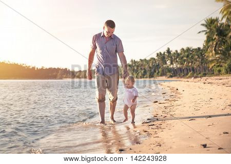 Father and child walking together on the beach coast during sunset with shining sea on background. Father holding child hand