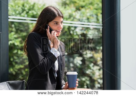 Young Businesswoman Holding Disposal Cup Talking On Mobile Phone