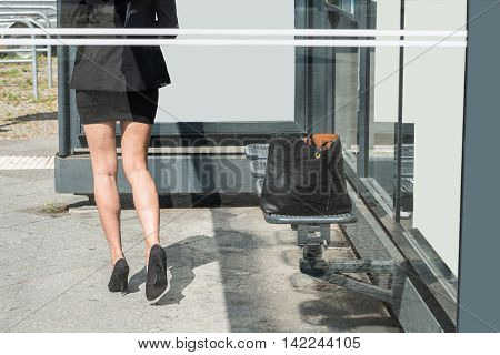 Close-up Of A Businesswoman Walking Forward With Black Handbag Left On Bench