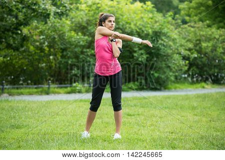Young Woman Stretching Her Hands While Exercising In Park