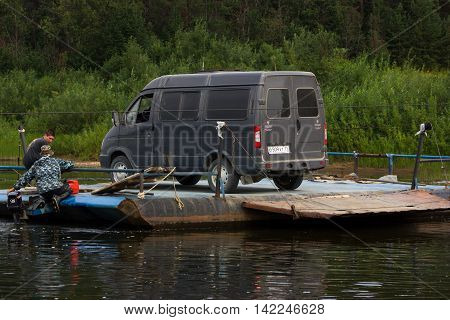 Borovskaya Russia - 22.07.2016: ferryman tranports minibus throw the river on handmade ferryboat