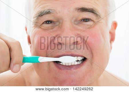 Senior Man Brushing His Teeth With Toothbrush