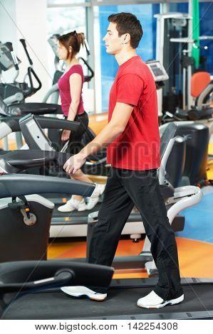 positive man at legs exercises machine