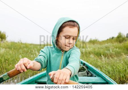boy on a row boat reached the shore.  boy controls a wooden rowing boat