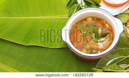 Spicy pork neck grilled Soup background Thai Isan favorite herbal green food for diet control have eat with noodle vegetable lemonThai morning glory all on banana leaf and left area for your word. poster