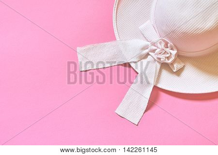 Women's hat with ribbon on pink background. Flat lay with plenty of copy space